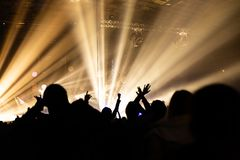 Silhouette of a concert crowd. The audience looks towards the stage. Party people at a rock concert. Musical party. Musical show. Group silhouette. Young stock image