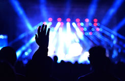 Silhouette of concert crowd in front of stage lights. Silhouette of concert crowd in front of bright stage lights Stock Photos