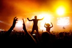 Silhouette Concert Person on Shoulders in Crowd with hands up at a Music Festival - Backlit with Lighting. Silhouette Concert Person, Man on Shoulders in Crowd Stock Photo