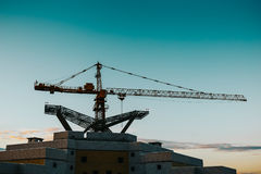 Silhouette of a construction crane over a high-rise building. Toned Stock Photography