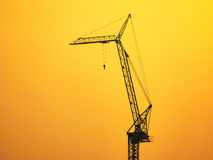 Silhouette of construction crane on sunset sky Stock Photography