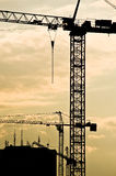 Construction cranes at sundown. Silhouetted construction cranes over modern buildings at sundown with cloudscape background Royalty Free Stock Image