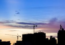 Silhouette Construction site with cranes Against Cloudy Sky at S Stock Photo