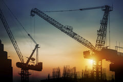 Silhouette construction site with cranes at sunset. For design work Stock Images