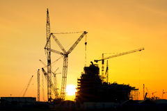 Silhouette of construction site in sunset time Stock Photos