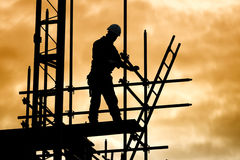 Silhouette construction worker on scaffolding building site. Silhouette of construction worker against sky on scaffolding with ladder on building site at sunset Royalty Free Stock Photos