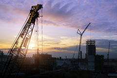 Silhouette construction. Silhouette construction worker , tower cranes build large residential buildings  at construction site industry Stock Photo