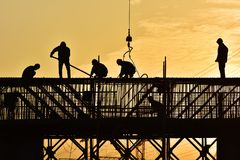 Silhouette of construction workers. The silhouette of a hard-working builder in the setting sun Royalty Free Stock Photos