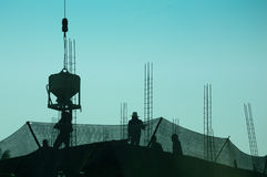 Silhouette of construction. Workers on scaffolding working under the blue sky Royalty Free Stock Photo