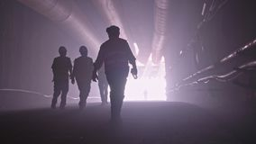 Silhouette of many construction workers walking out from a large tunnel stock footage