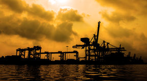 Silhouette of Container Cargo freight ship with working crane. Royalty Free Stock Image