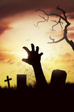 Silhouette corpse raising hands from his grave on the cemetery royalty free stock photos