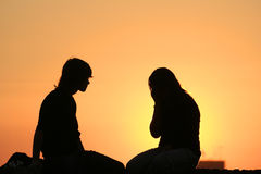 Silhouette couple 1. Silhouette of a couple at sunset sitting and looking at the horizon stock image