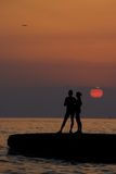 A silhouette couple-1. A silhouette couple looking standing on the beach as the sun is setting stock images