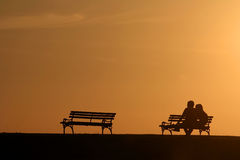 Silhouette couple. Silhouette of a couple at sunset sitting and looking at the horizon stock photography