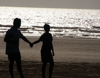 Silhouette Couple. A silhouette of a young couple holding hands on the beach Royalty Free Stock Image