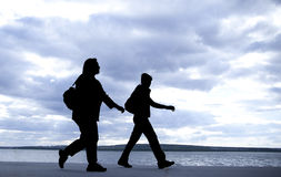 Silhouette of couple. Silhouette of homosexual couple taking and walk on a beach shore in sunset light Royalty Free Stock Image