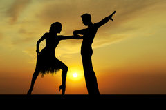 Silhouette couple in the active ballroom dance on sunset. Dance silhouette couple dancing ballroom dancing on sunset  background Stock Photo
