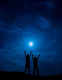 Silhouette of couple against full moon with hands up Royalty Free Stock Photo