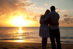 Silhouette of couple on a beach at sunset stock images
