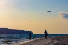 Silhouette of couple on beach on sunset sky background with airplane during for landing stock photos