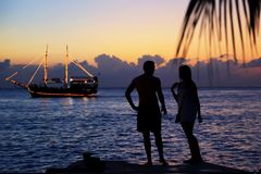 Silhouette of couple at the beach during sunset. Vacation concept stock photography