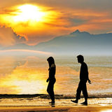 Silhouette of a couple on the beach. Silhouette of a couple at sunset walking along Seattle beach Stock Photo
