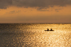 Silhouette of a couple on a canoe boat during sunset. Silhouette of two people on a kayak at sea beach at twilight time Stock Images
