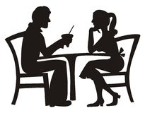 Silhouette of couple dating. An artistic view with silhouettes of young man and woman sitting at a table, sharing a soda while on a date Stock Photos