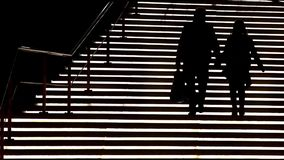 Silhouette of a couple descending a staircase light stock video