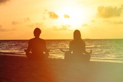 Silhouette of couple doing yoga at sunset Royalty Free Stock Photography