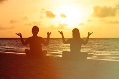Silhouette of couple doing yoga at sunset Royalty Free Stock Images