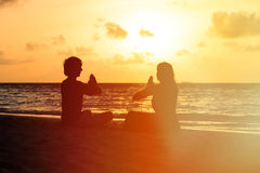 Silhouette of couple doing yoga at sunset. Beach stock images