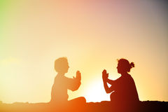 Silhouette of couple doing yoga at sunset. Sky stock photography
