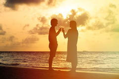 Silhouette of couple drinking wine at sunset beach Royalty Free Stock Photo