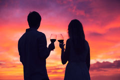 Silhouette of couple drinking wine at sunset Stock Photo