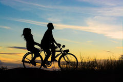 Silhouette of couple driving bike happy time sunset Royalty Free Stock Photos