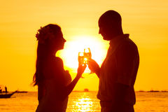 Silhouette of couple enjoying glass of champagne on tropical bea Stock Image