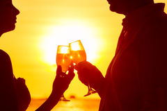 Silhouette of couple enjoying glass of champagne on tropical beach at sunset.  royalty free stock photos