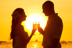 Silhouette of couple enjoying glass of champagne on tropical beach at sunset.  stock image