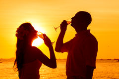 Silhouette of couple enjoying glass of champagne on tropical beach at sunset.  royalty free stock image