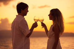 Silhouette of couple enjoying glass of champagne on tropical beach. At sunset stock photography