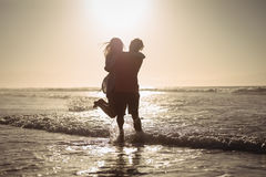 Silhouette couple enjoying on shore at beach. During sunny day Stock Photography