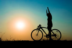 Silhouette couple. Silhouette of a girl and her bike on meadow at the sunset time. Standing and hand up while riding. Have a beauty blue sky and white - pink of Stock Photos