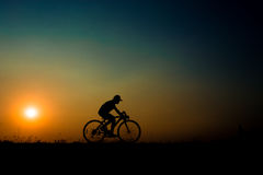 Silhouette couple. Silhouette of girl at the sunset time on meadow riding a bike have background of a beauty yellow and blue sky and white of a sun Stock Image