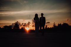silhouette couple of guy kiss girl on sand in classic dress. trees and sky on background royalty free stock image