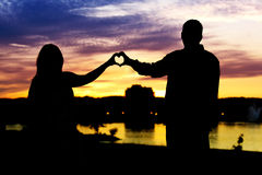 Silhouette of couple heart shaped. A loving couple create a heart shaped silhouette royalty free stock photography