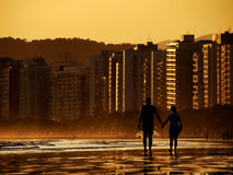Silhouette of couple holding hands. Walking on the beach stock image