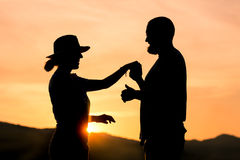 silhouette of a couple holding hands at golden hour stock image