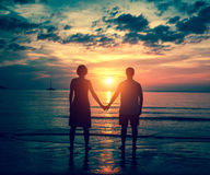 Silhouette of couple holding hands on the sea beach Stock Photography